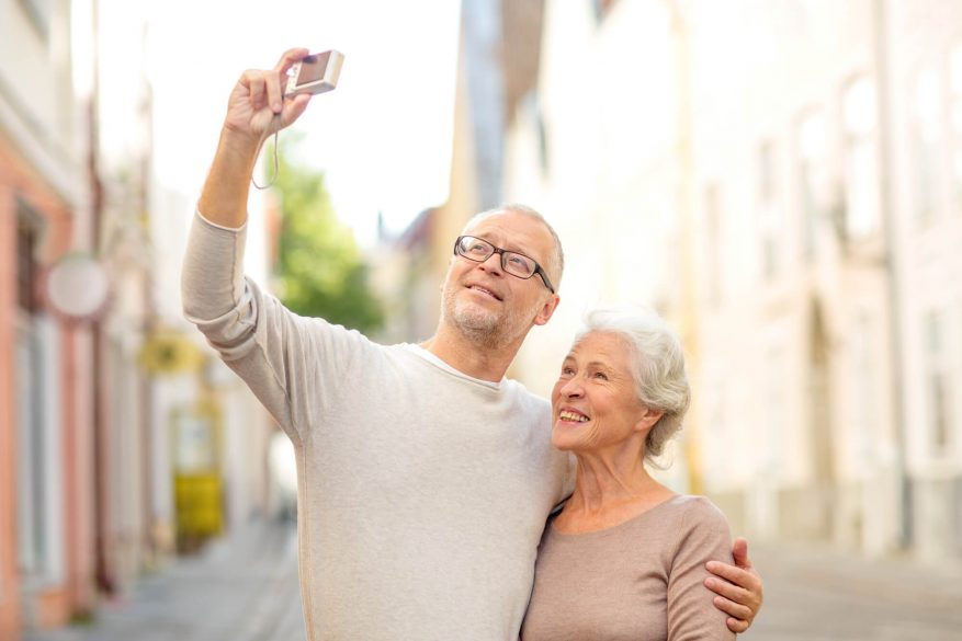 senior man and woman taking a photo with a digital camera on vacation