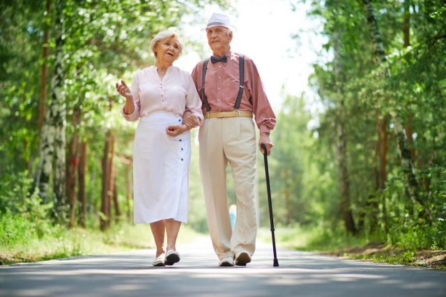 senior man and woman walking in the park with safe shoes