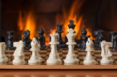 chess board with large sized pieces in front of a roaring fire