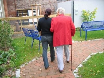 senior woman walking with the help of a cane and a family member