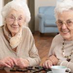 two elderly ladies enjoying a large print game