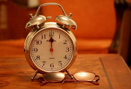 alarm clock next to a pair of reading glasses