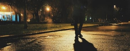 elderly person walking at night