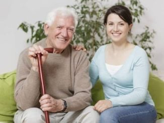 man sitting on couch with daughter while holding his cane