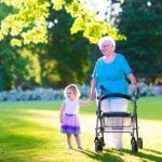 grandmother and grandaughter walking in park with a 4 wheel walker with seat