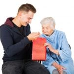 man giving give to elderly lady with dementia