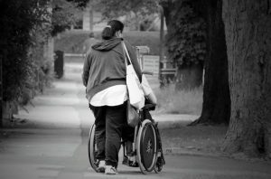 elderly woman being pushed in a manual wheelchair
