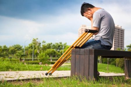 injured man on crutches sitting on a bench