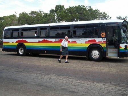 senior man getting on a tour bus