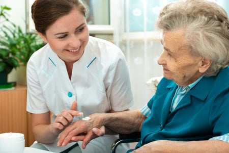 nurse assists an elderly woman with putting on lotion at home