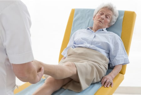 senior woman getting ankle examined