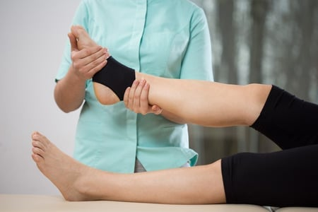 THerapist stretching a painful ankle