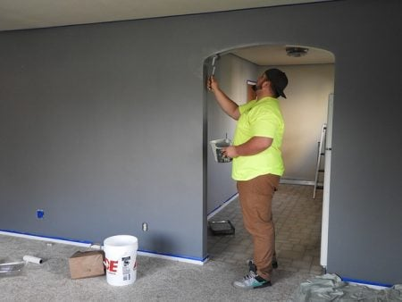 man painting the home of an elderly person