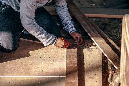 man measuring and cutting wood