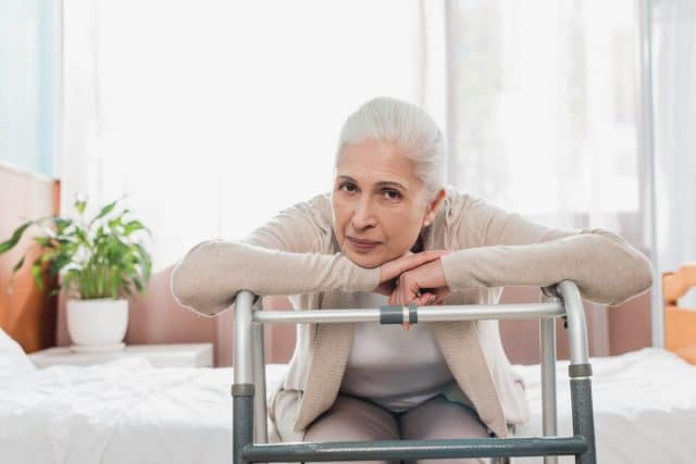attractive senior woman leaning on a walker