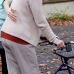 nurse helping elder person to walk with walker
