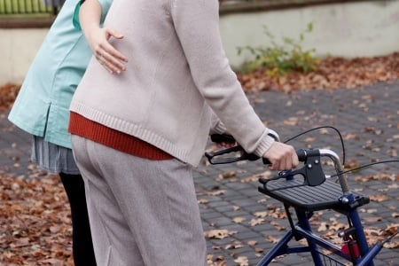 nurse helping elder person to walk with walker
