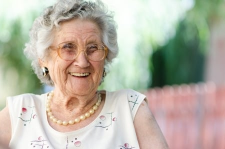 happy elderly lady with glasses smiling