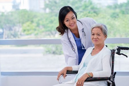 woman sitting in a rollator transport chair posing with her doctor