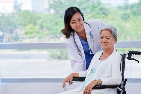 young female doctor with an elderly patient in a transport wheelchair at the hospital.