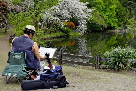 senior man painting in a japanese garden