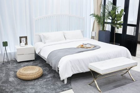 low platform bed with white comforters on a gray carpeted floor