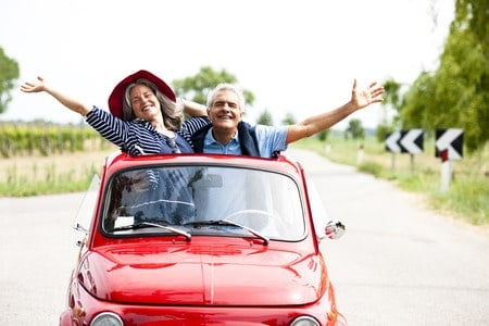 happy senior couple driving a bright red vintage car on vacation