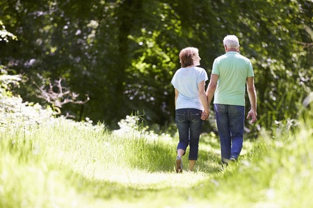 rear view of senior couple walking in summer countryside