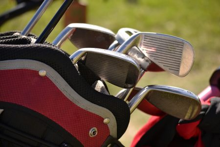 close up of golf club heads in a red and black bag with the course in the background
