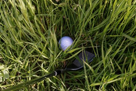 golf ball stuck in deep grass with the head of a pitching wedge next to it