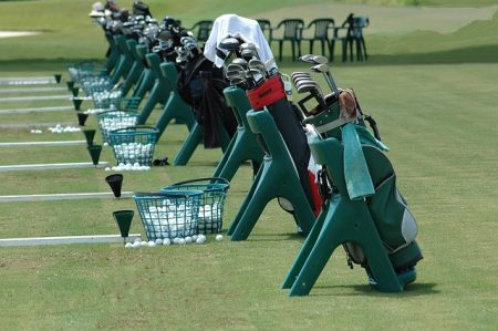golf club bags lined up at a driving range