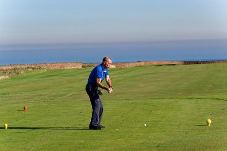 senior man in golf attire teeing off with ocean in the background