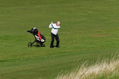 senior golfer swinging a wedge on the fairway with his bag beside him
