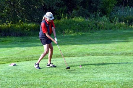 senior lady in shorts and a golf hat teeing off with a driver
