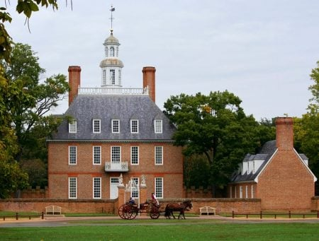 large brick colonial home with stable house and a horse drawn carriage out front
