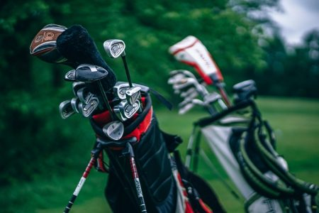 two sets of golf clubs in golf bags on stands with green trees in background