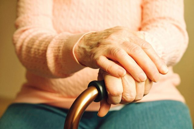 close up of a senior woman's hand holding onto the handle of a quad cane