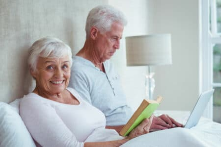 senior couple reading in bed with lamp lighting