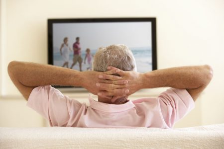 senior man relaxing and watching TV with his hands behind his head