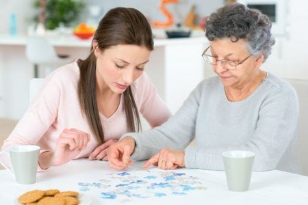 senior woman with dementia working a puzzle with her granddaughter