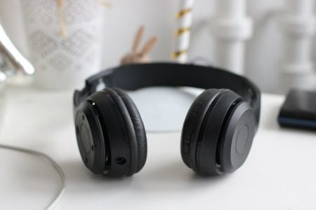 pair of black headphones laying on a white desk