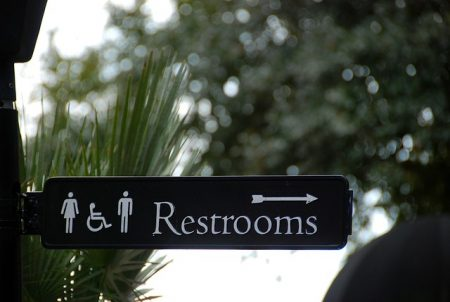 sign pointing to public restrooms with trees in the background