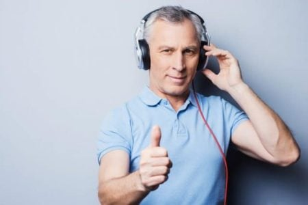 portrait of senior man in headphones listening to music and showing his thumb up while standing against grey background