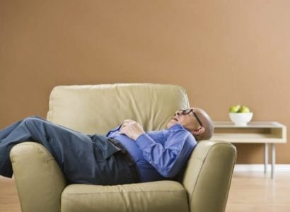 Senior man sleeping on chair with glasses on and hands folded on chest.