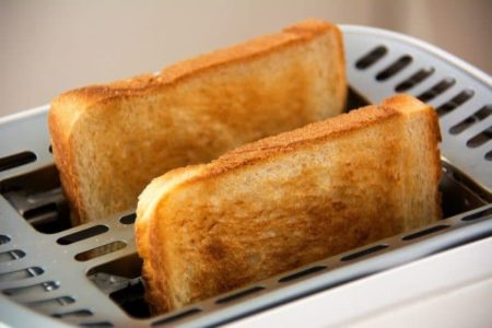 two slices of perfectly toasted toast coming out of the top of a toaster