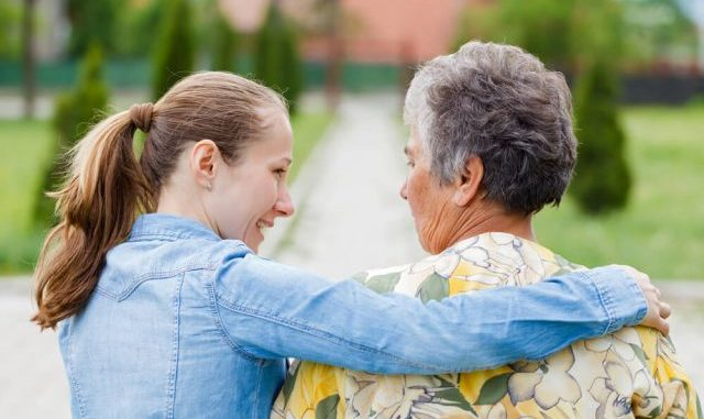 senior walking with her caregiver from the back view