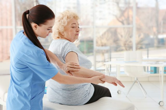 senior woman having her elbow examined by a physical therapist