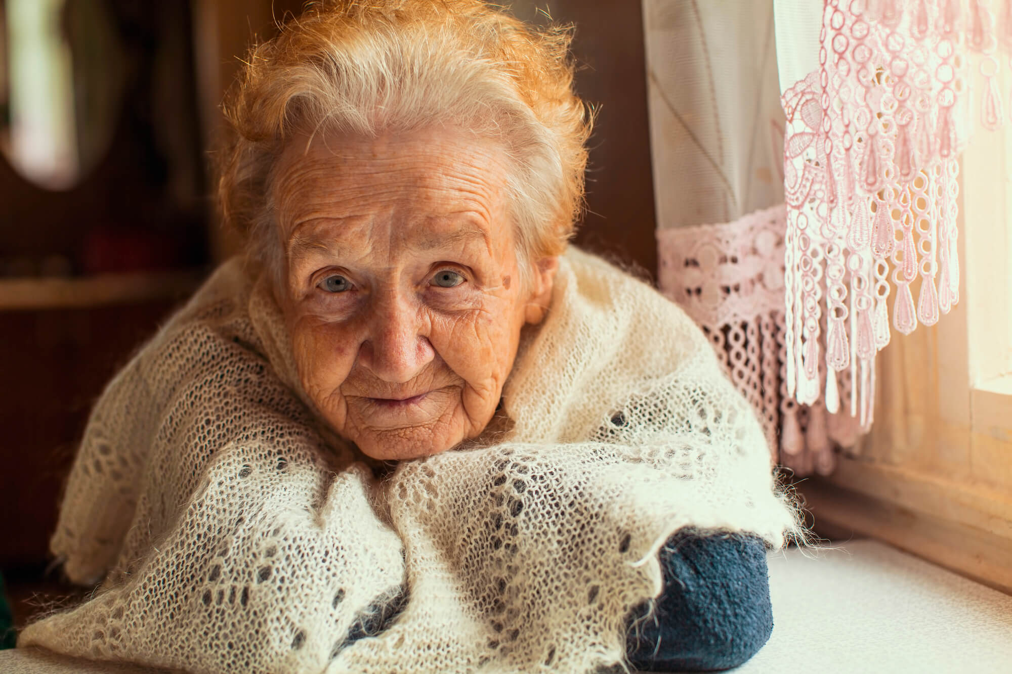elderly woman with white hair wrapped up in a knitted shawl looking at the camera