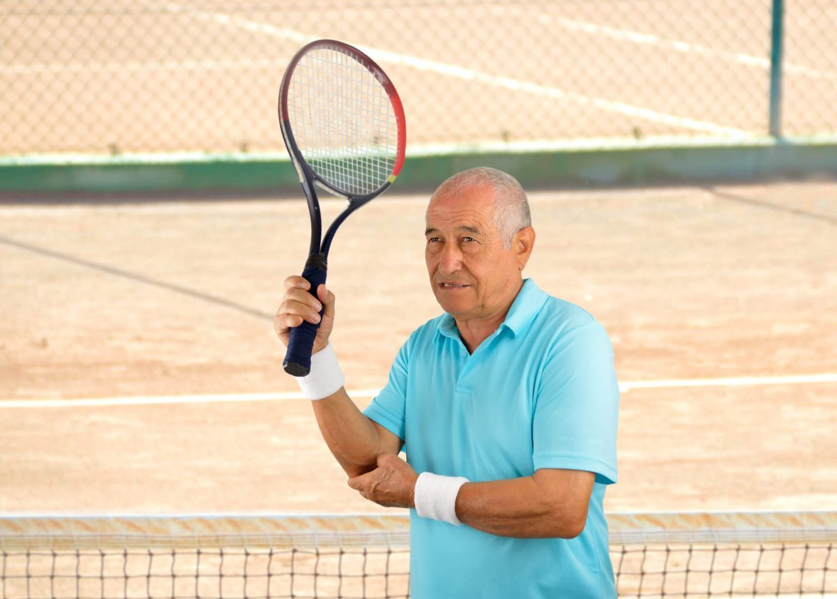 senior man playing tennis holding his painful elbow