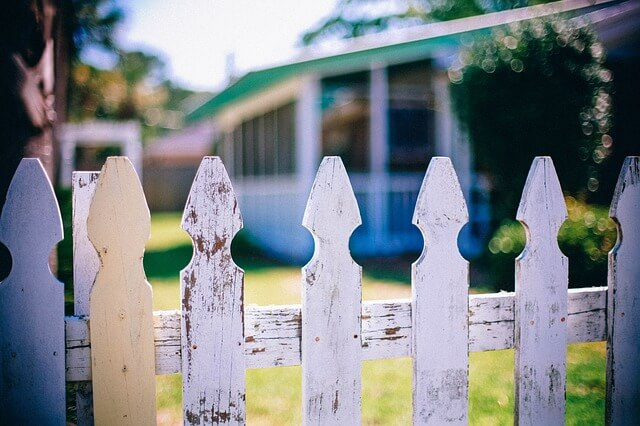 close up of a white dilapidated fence with an older house in the background.